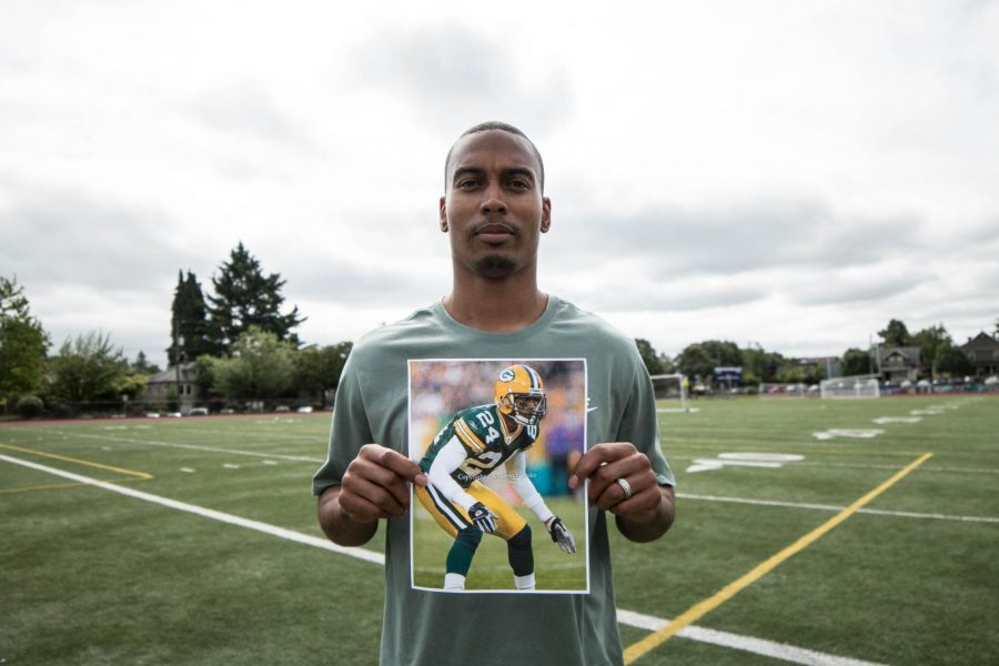 Coach Joey Thomas poses with an old photo of himself playing for the Packers.